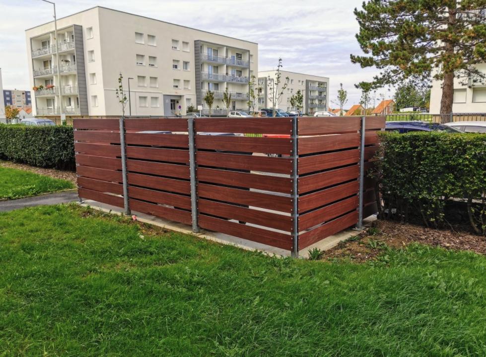 Voor een project bij een woonflat zijn is deze afscherming geplaatst. De afmetingen zijn 450 x 225 cm. De hoogte is 150 cm. Er zijn verstelbare palen gebruikt en HPL planken in de donkere kleur Mahony. Er passen